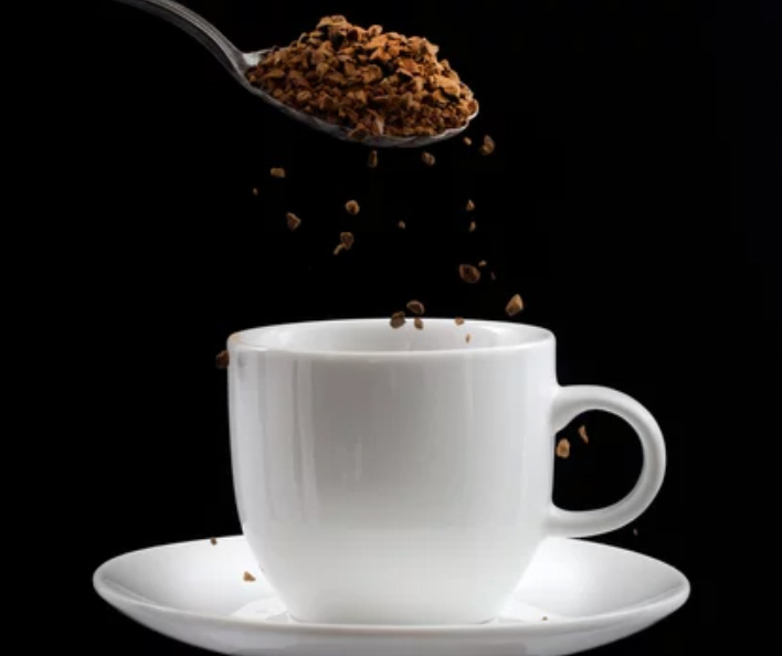 instant coffee being poured into cold water